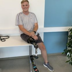 Photo: Alex Böhmer sitting on a bench with running prosthesis and sportswear; Copyright: privat