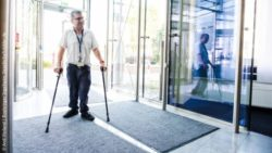 Photo: Employee with crutches in the entrance area of the company headquarters/office building; Copyright: Andi Weiland | Boehringer Ingelheim, Gesellschaftsbilder.de