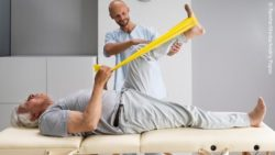 Image: A physiotherapist is doing exercises for the knee with an older man; Copyright: PantherMedia/Andriy Popov