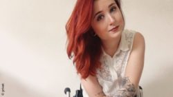 Photo: Portrait of a young woman with red hair and tattooed arms in a wheelchair - Luisa L'Audace; Copyright: privat