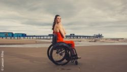 Photo: Samanta Bullock in her wheelchair at the beach. She is wearing a chic red dress; Copyright: Lawson Filho
