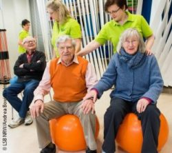 Photo: A man and a woman are sitting on a pezzi ball, two trainers are standing behind them.; Copyright: LSB NRW/Andrea Bowinkelmann