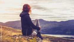 Photo: Woman sitting on a rock in peace with herself; Copyright: PantherMedia/lofilolo