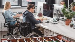 Photo: Several employees in an office. One of them is using a wheelchair; Copyright: PantherMedia/ArturVerkhovetskiy