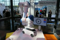 Photo: Robot arm holds a small white car; Copyright: beta-web/Schlüter