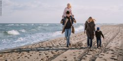 Photo: a family at the beach, the mother is holding a child's hand, the father is carrying a second child on his shoulders; Copyright: PantherMedia / VaDrobotBO