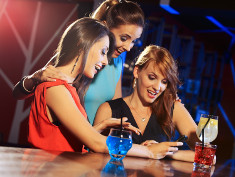 Photo: Young adults using a smartphone and drinking