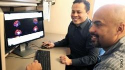 Photo: Researchers Damien Fair and Oscar Miranda Rodriguez in front of a computer monitor; Copyright: OHSU