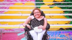 Photo: a woman in white jeans and black top – Evelyn Brezina – is sitting in a wheelchair which is placed in front of multi-coloured stairs; Copyright: Lucia Titkova