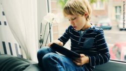 Photo: Autistic boy sitting on a windowsill and using a tablet; Copyright: PantherMedia/Dubova
